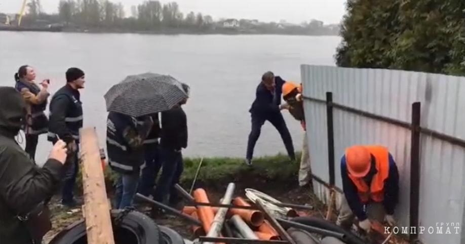 Валерий Цветков толкает сотрудника и роняет забор