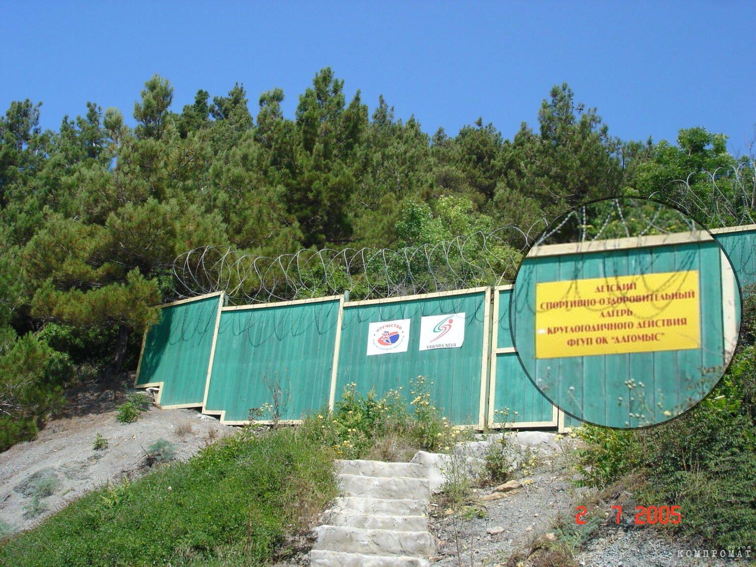 Табличка с логотипом клуба дзюдо «Явара-Нева» и табличка о детском лагере на изгороди дворца-долгостроя